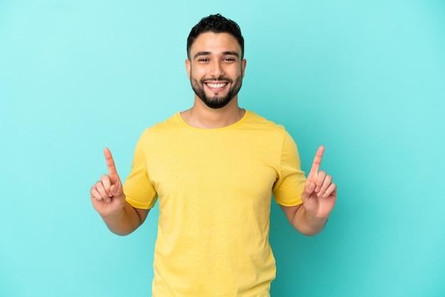 Молодой арабский мужчина изолирован на синем фоне, указывая на отличную идею