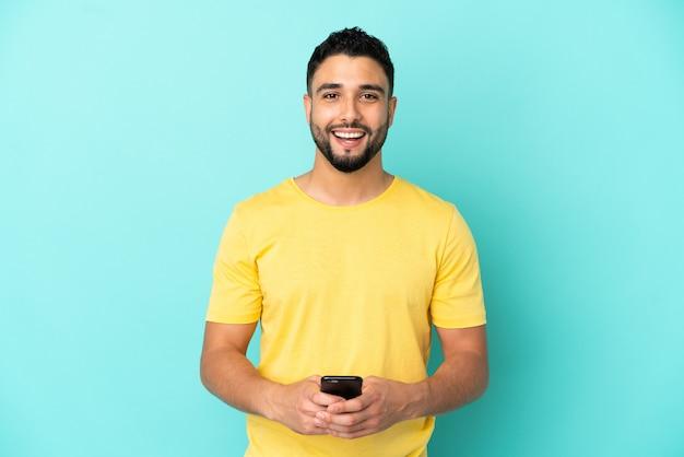 Молодой арабский мужчина, изолированные на синем фоне, удивлен и отправляет сообщение