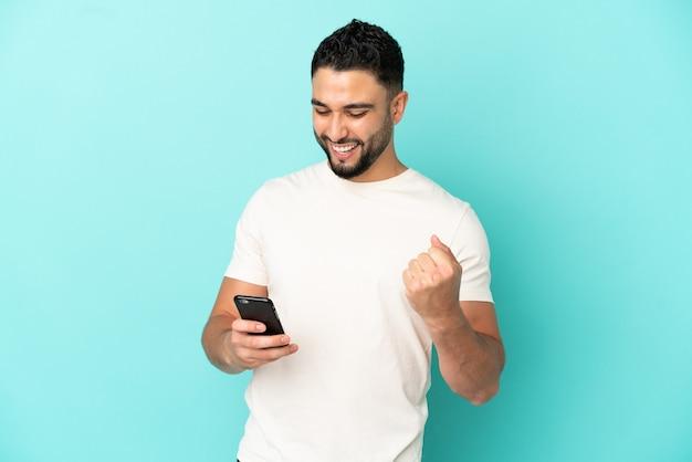 Молодой арабский человек изолирован на синем фоне с телефоном в позиции победы