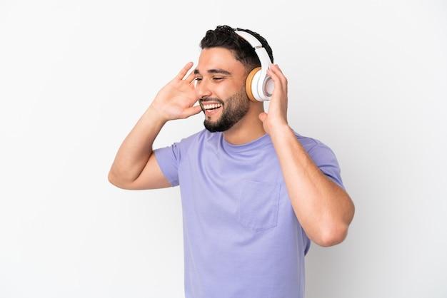 Молодой арабский человек, изолированные на белом фоне, слушает музыку и поет