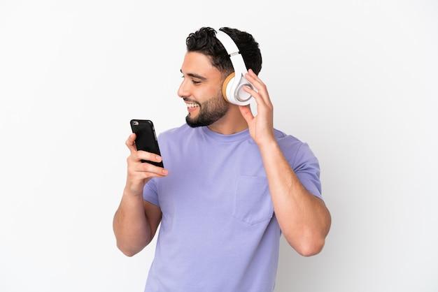 Молодой арабский человек, изолированные на белом фоне, слушает музыку с помощью мобильного телефона и поет
