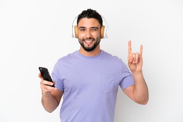 Молодой арабский человек, изолированные на белом фоне, слушает музыку с помощью мобильного телефона, делая рок-жест