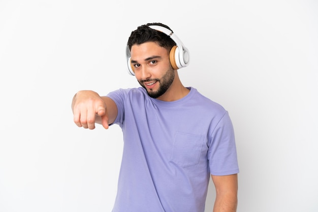 Молодой арабский человек, изолированные на белом фоне, слушая музыку
