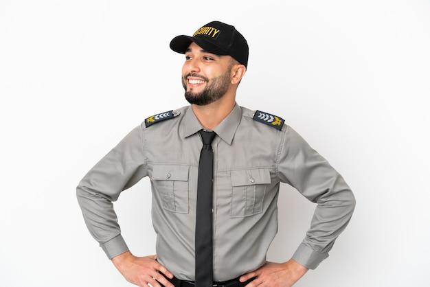 Молодой арабский мужчина на белом фоне позирует с руками на бедрах и улыбается