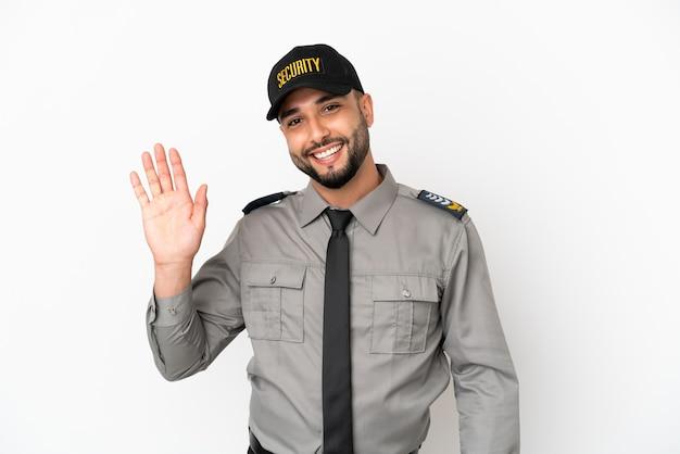 Молодой арабский человек изолирован на белом фоне, салютуя рукой с счастливым выражением лица