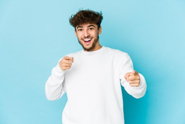 Молодой арабский человек на голубых, веселых улыбках, указывающих вперед.