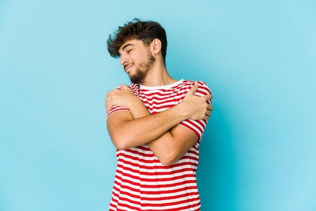 파란색 벽에 젊은 아랍 남자 포옹, 평온하고 행복 미소