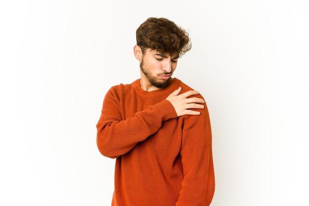 Молодой арабский человек на белой стене с болью в плече