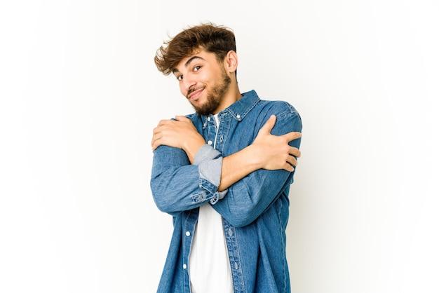 흰 벽에 젊은 아랍 남자 포옹, 평온하고 행복 미소