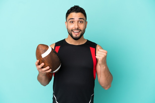 Young arab man playing rugby isolated on blue background celebrating a victory in winner position