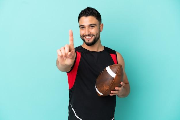 青の背景に分離されたラグビーをしている若いアラブ人が指を見せて持ち上げる