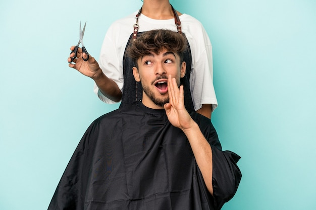 Young arab man ready to get a haircut isolated on blue background is saying a secret hot braking news and looking aside