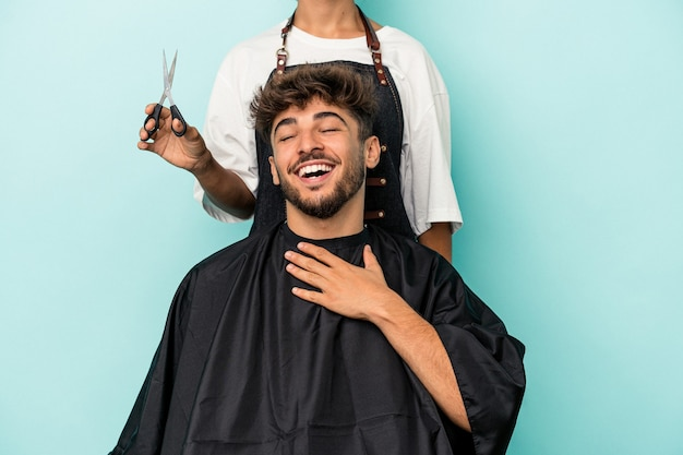 Young arab man ready to get a haircut isolated on blue background laughs out loudly keeping hand on chest.