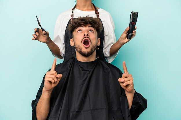 Young arab man ready to get a haircut isolated on blue background pointing upside with opened mouth.