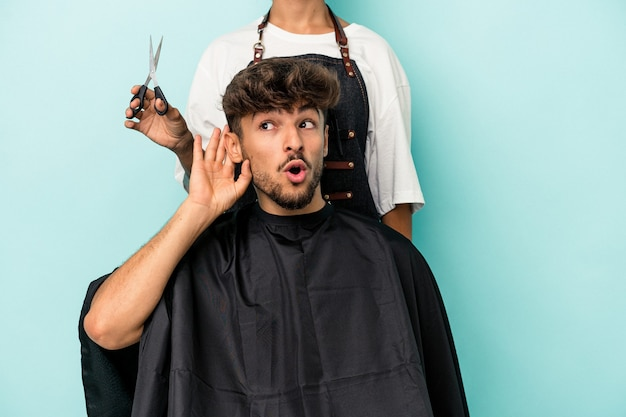 Young arab man ready to get a haircut isolated on blue background trying to listening a gossip.