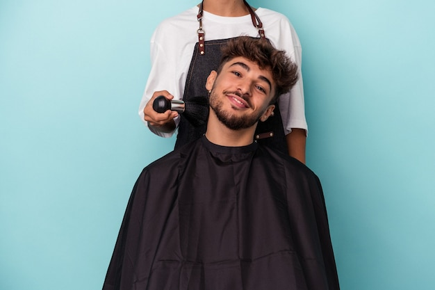 Young arab man ready to get a haircut isolated on blue background