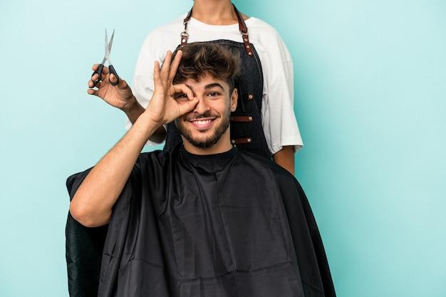 若いアラブ人は、青い背景で髪型を分離する準備ができて興奮し、目のジェスチャーを維持します。