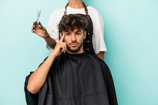 若いアラブ人は、指で寺院を指して、タスクに焦点を当てて、青い背景に散髪を分離する準備ができています。