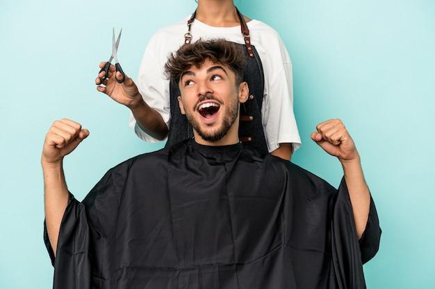 勝利、勝者の概念の後に拳を上げる青い背景に散髪を分離する準備ができている若いアラブ人。