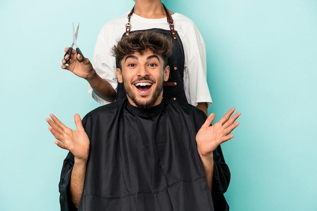 若いアラブ人は、青い背景に散髪を分離する準備ができて、嬉しい驚きを受け取り、興奮し、手を上げます。