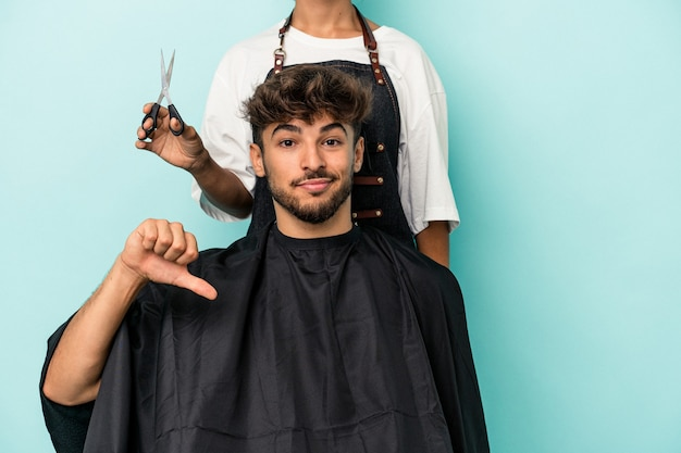 嫌いなジェスチャーを示す青い背景に散髪を分離する準備ができている若いアラブ人は、親指を下に向けます。不一致の概念。