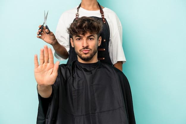 若いアラブ人は、一時停止の標識を示す伸ばした手で立っている青い背景に散髪を分離する準備ができて、あなたを防ぎます。