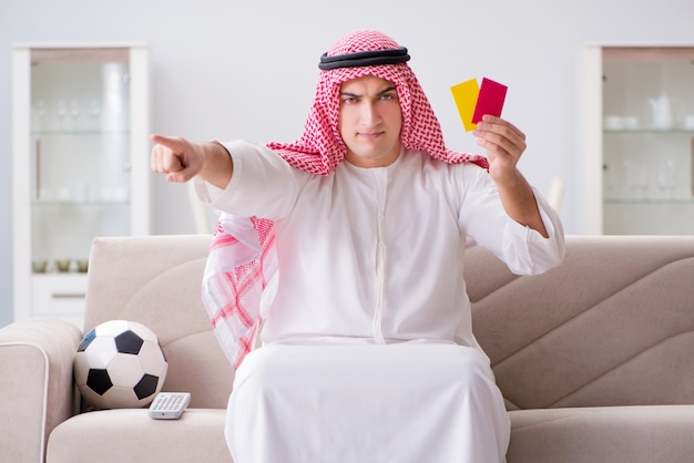 Young arab man watching football sitting on sofa