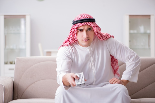 Young arab man watching tv sitting on the sofa