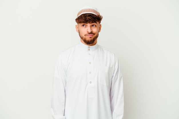 白い背景で隔離の典型的なアラビアの衣装を着ている若いアラブ人は混乱し、疑わしく、不安を感じます。