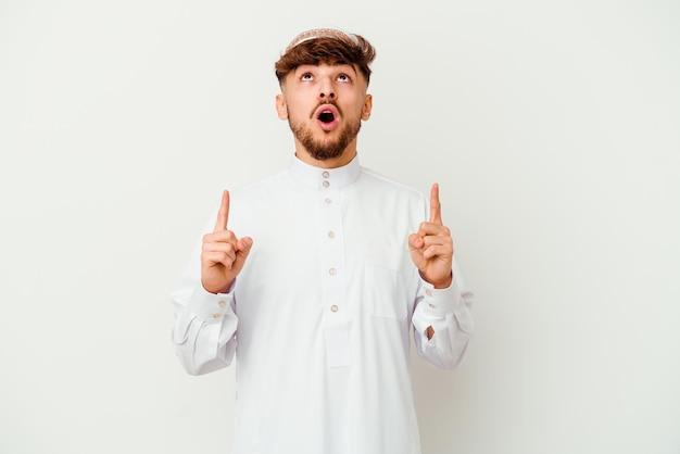 열린 된 입으로 거꾸로 가리키는 흰색 절연 전형적인 아랍어 의상을 입고 젊은 아랍 남자.