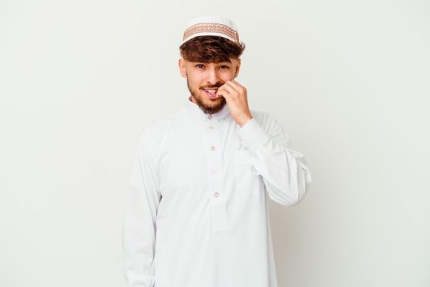 指の爪を噛む白い壁に隔離された典型的なアラビアの衣装を着て、神経質で非常に心配している若いアラブ人。