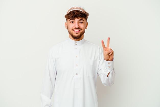 指で2番目を示す白い壁に分離された典型的なアラビアの衣装を着ている若いアラブ人。
