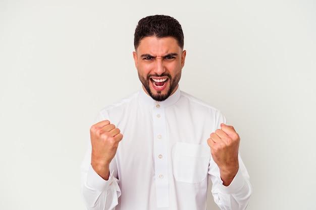 のんびりと興奮して応援している白い背景で隔離の典型的なアラブの服を着ている若いアラブ人。勝利の概念。