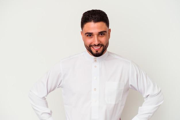 白い背景に分離された典型的なアラブの服を着た若いアラブ人は、腰に手を当て続ける自信を持っています。