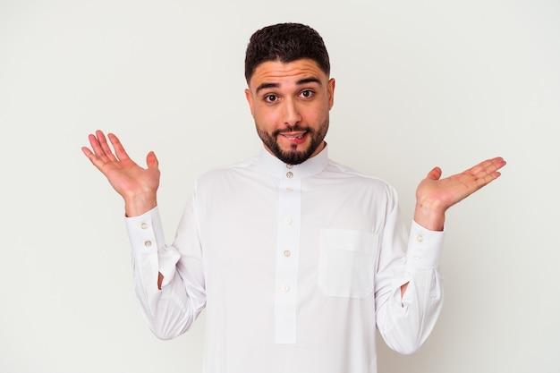白い背景で隔離された典型的なアラブの服を着ている若いアラブ人は、コピースペースを保持するために混乱し、疑わしい肩をすくめる肩をします。