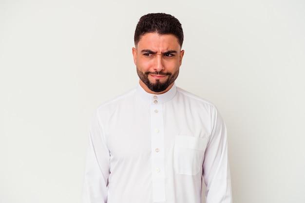 白い背景で隔離の典型的なアラブの服を着ている若いアラブ人は混乱し、疑わしく、不安を感じます。