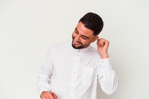白い背景で隔離の典型的なアラブの服を着て踊って楽しんでいる若いアラブ人。
