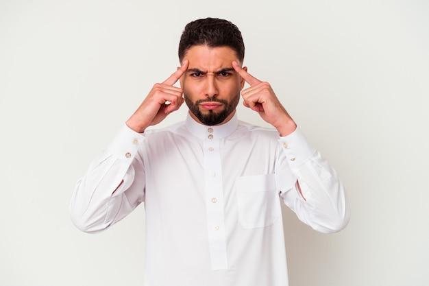 Молодой арабский мужчина в типичной арабской одежде на белом фоне сосредоточился на задаче, держа указательные пальцы, указывая головой.
