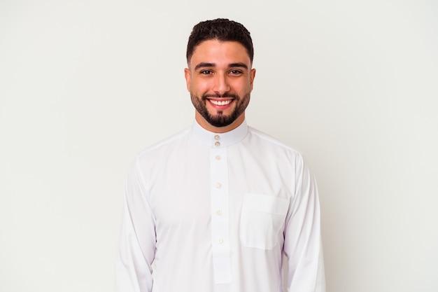 Молодой арабский мужчина в типичной арабской одежде на белом фоне счастлив, улыбается и весел.