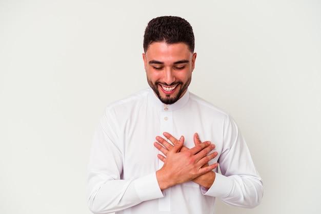 白い背景に典型的なアラブの服を着た若いアラブ人が、幸せの概念を胸に手をつないで笑いながら笑っている。