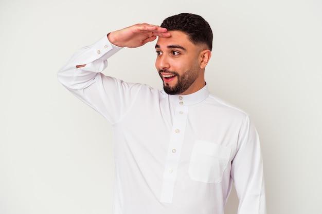 白い背景に典型的なアラブの服を着た若いアラブ人男性が、額に手を当てて遠くを見つめている。