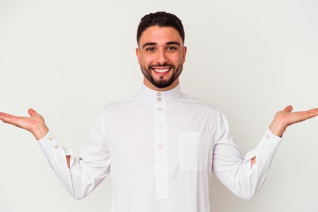 白い背景に典型的なアラブの服を着た若いアラブ人は、腕でスケールを作り、幸せで自信を感じます。