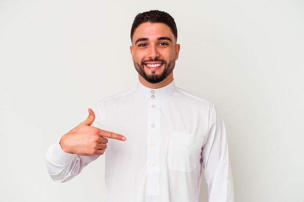 白い背景に典型的なアラブの服を着た若いアラブ人男性が、シャツのコピースペースを手で指し、誇りと自信を持って