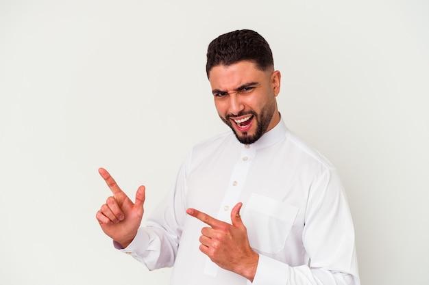 Молодой арабский мужчина в типичной арабской одежде на белом фоне, указывая указательными пальцами на место для копирования, выражая волнение и желание.