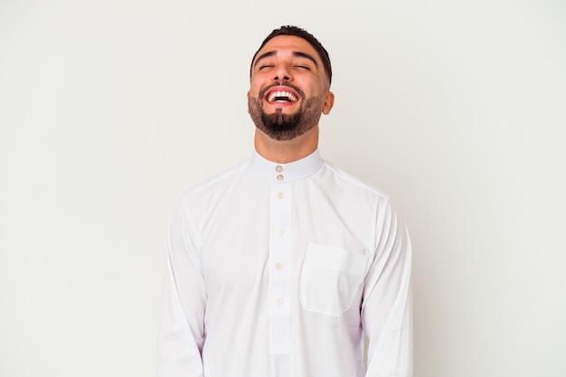 白い背景に典型的なアラブの服を着た若いアラブ人は、リラックスして幸せに笑い、首を伸ばして歯を見せた。