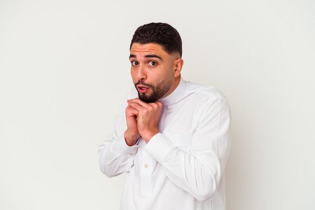 白い背景で隔離の典型的なアラブの服を着ている若いアラブ人は怖くて恐れています。