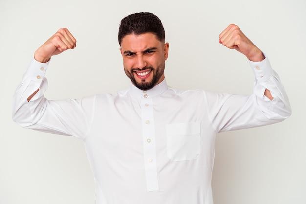 Молодой арабский мужчина в типичной арабской одежде на белом фоне показывает жест силы руками, символ женской силы