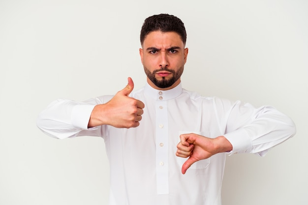 Молодой арабский мужчина в типичной арабской одежде на белом фоне показывает палец вверх и палец вниз, сложно выбрать концепцию