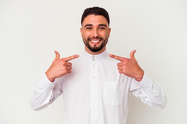 典型的なアラブの服を着た若いアラブ人が、白い背景に微笑み、口を指さしている。