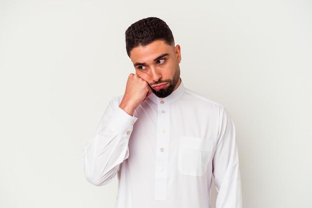 白い背景に典型的なアラブの服を着た若いアラブ人男性が、コピースペースを見て、悲しく物思いにふける。